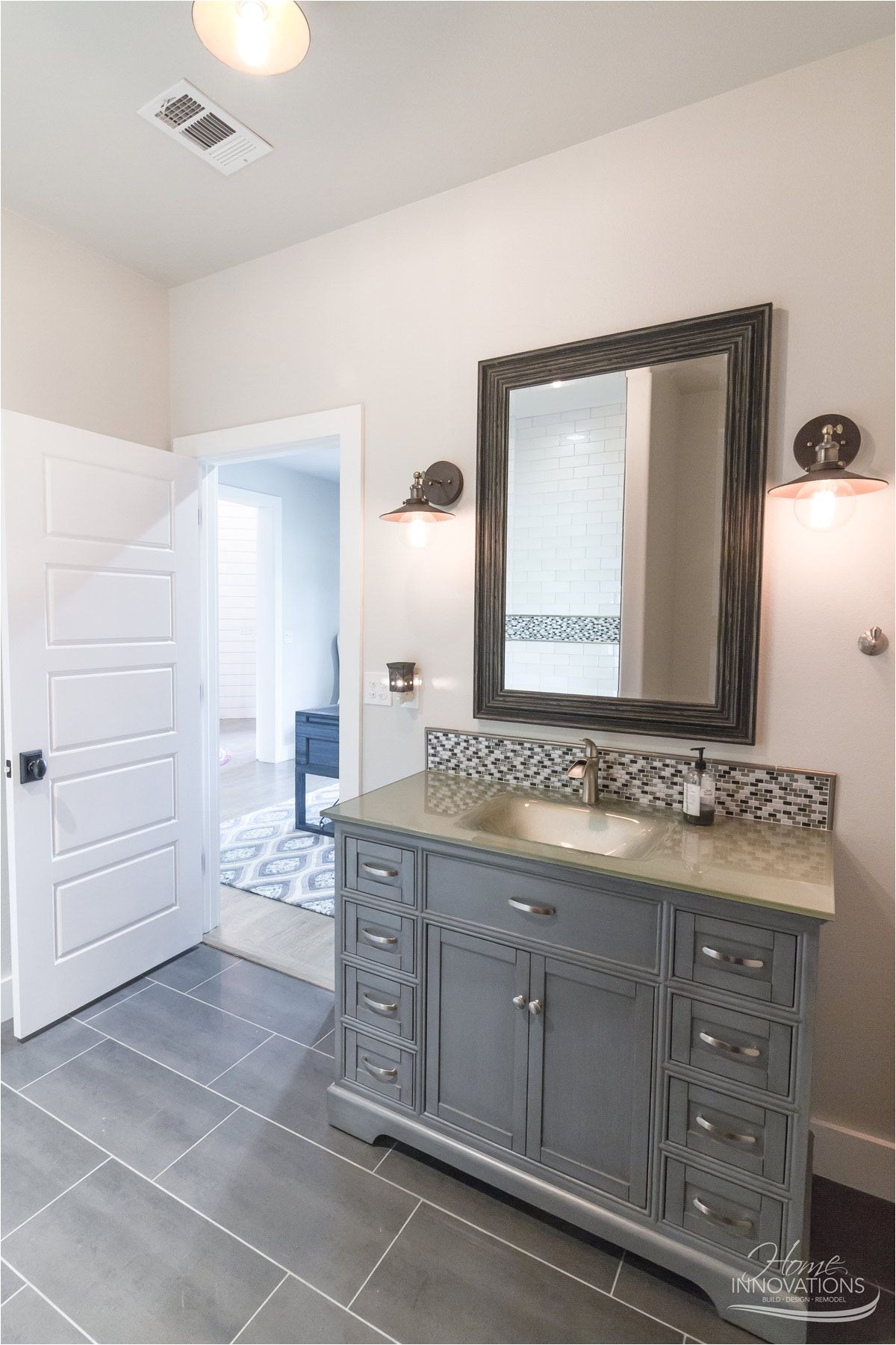 custom home builder tulsa ok bathroom with gray porcelain tile floor gray cabinets brushed nickel faucets oil rubbed bronze hanging sconces