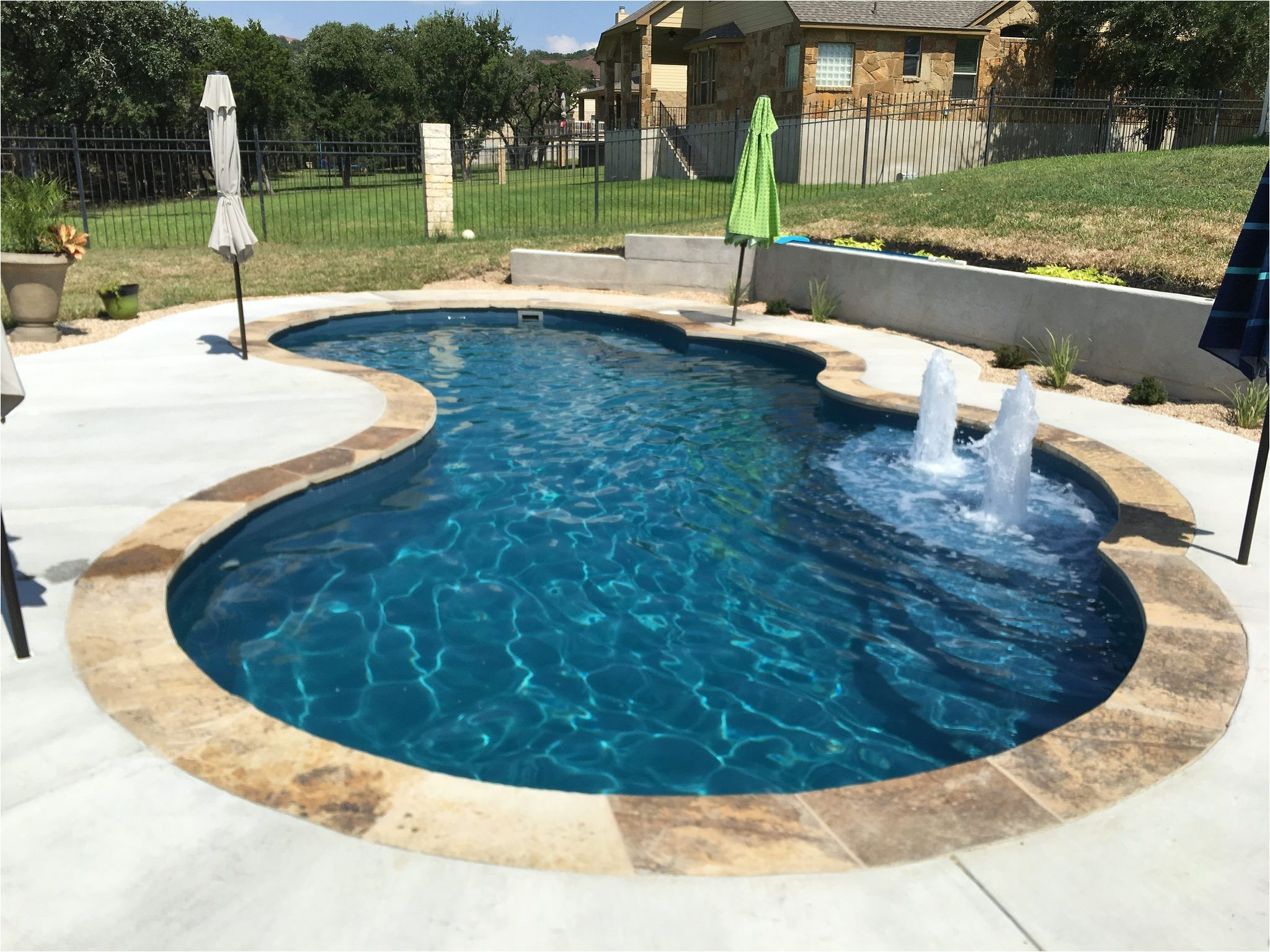 this 16 x 32 gemini shaped fiberglass inground pool complete in vega color sandstone coping and bubblers is perfect for your backyard upgrade