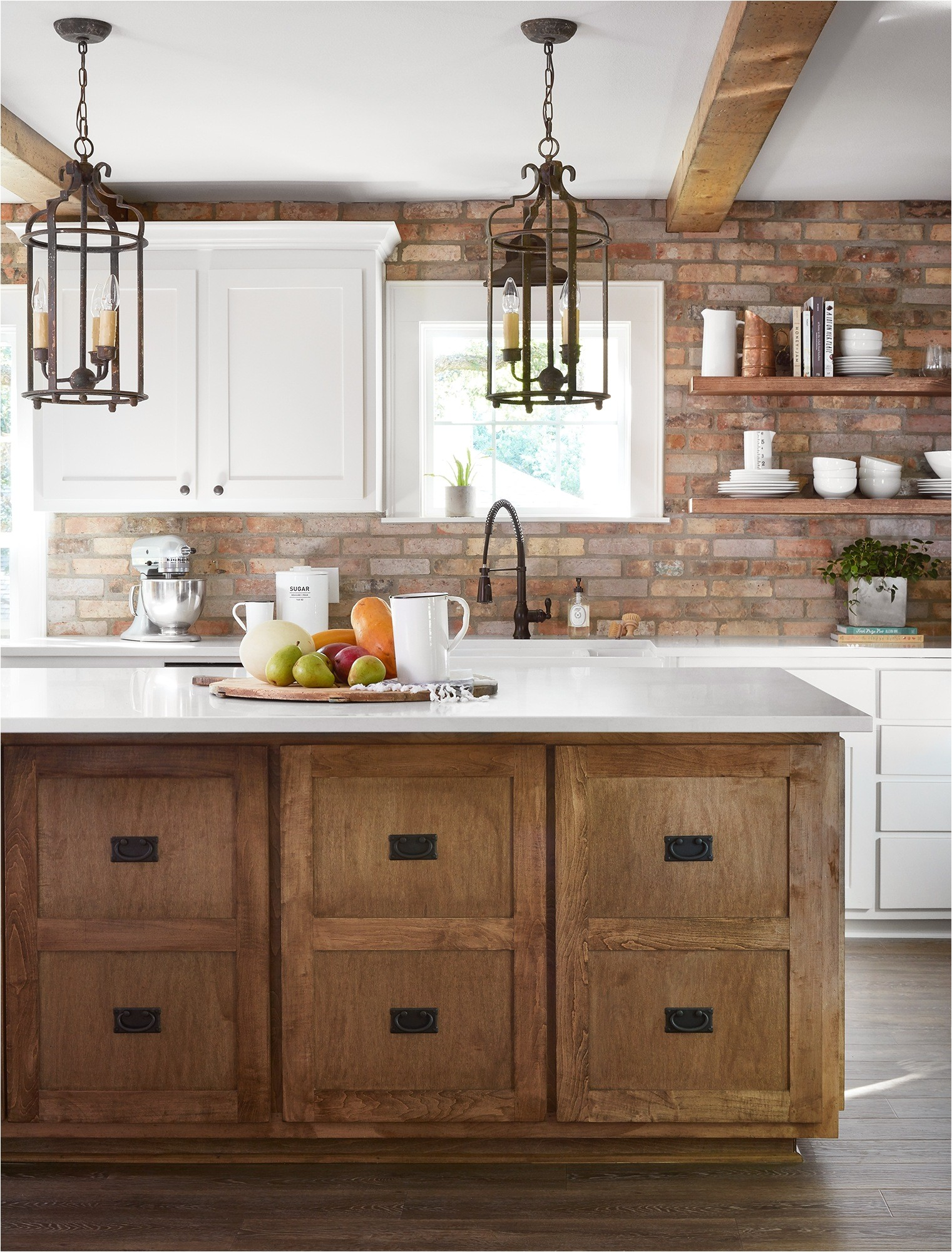 the client really wanted an antique brick backsplash so we carried it from countertops to ceiling to make a bold statement we kept the rest simple with