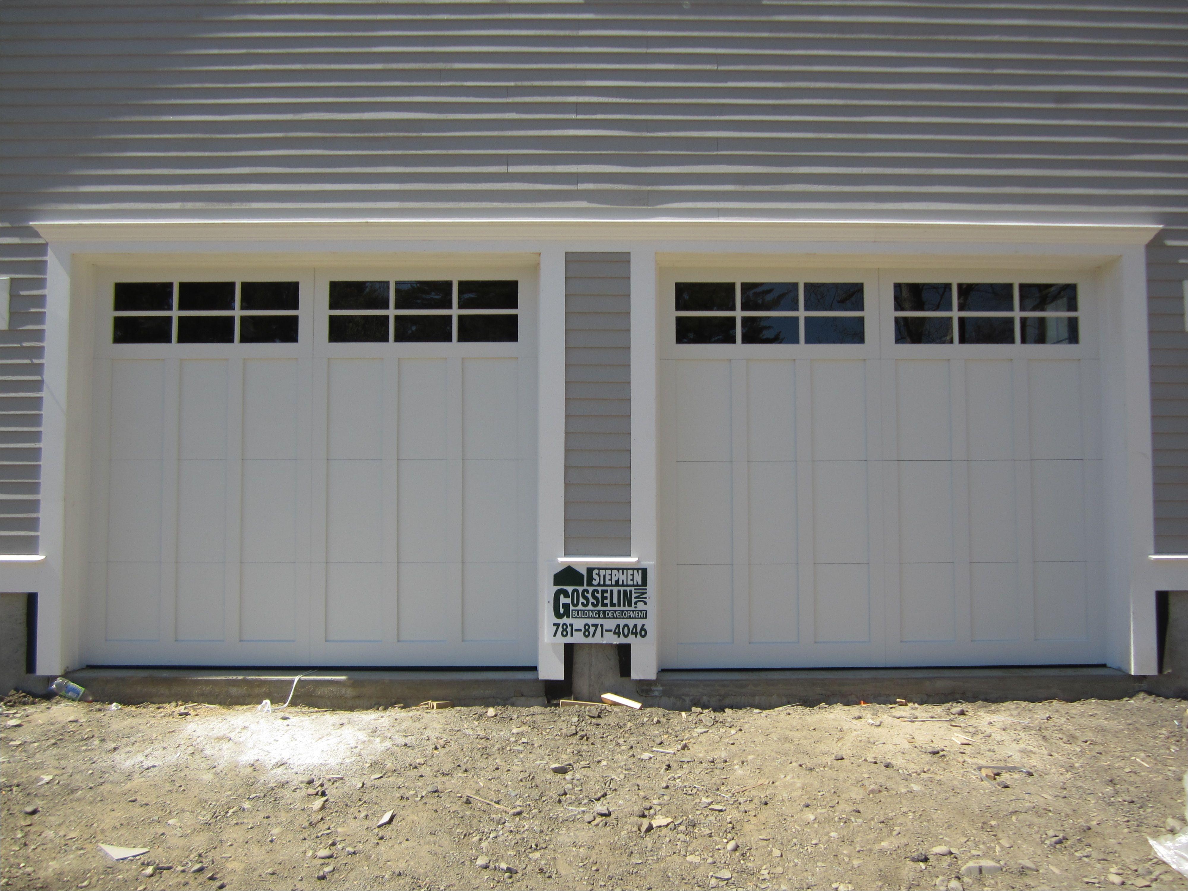 haas american tradition model 922 steel carriage house style garage doors in white with 6 pane glass installed by mortland overhead door mortlanddoor com