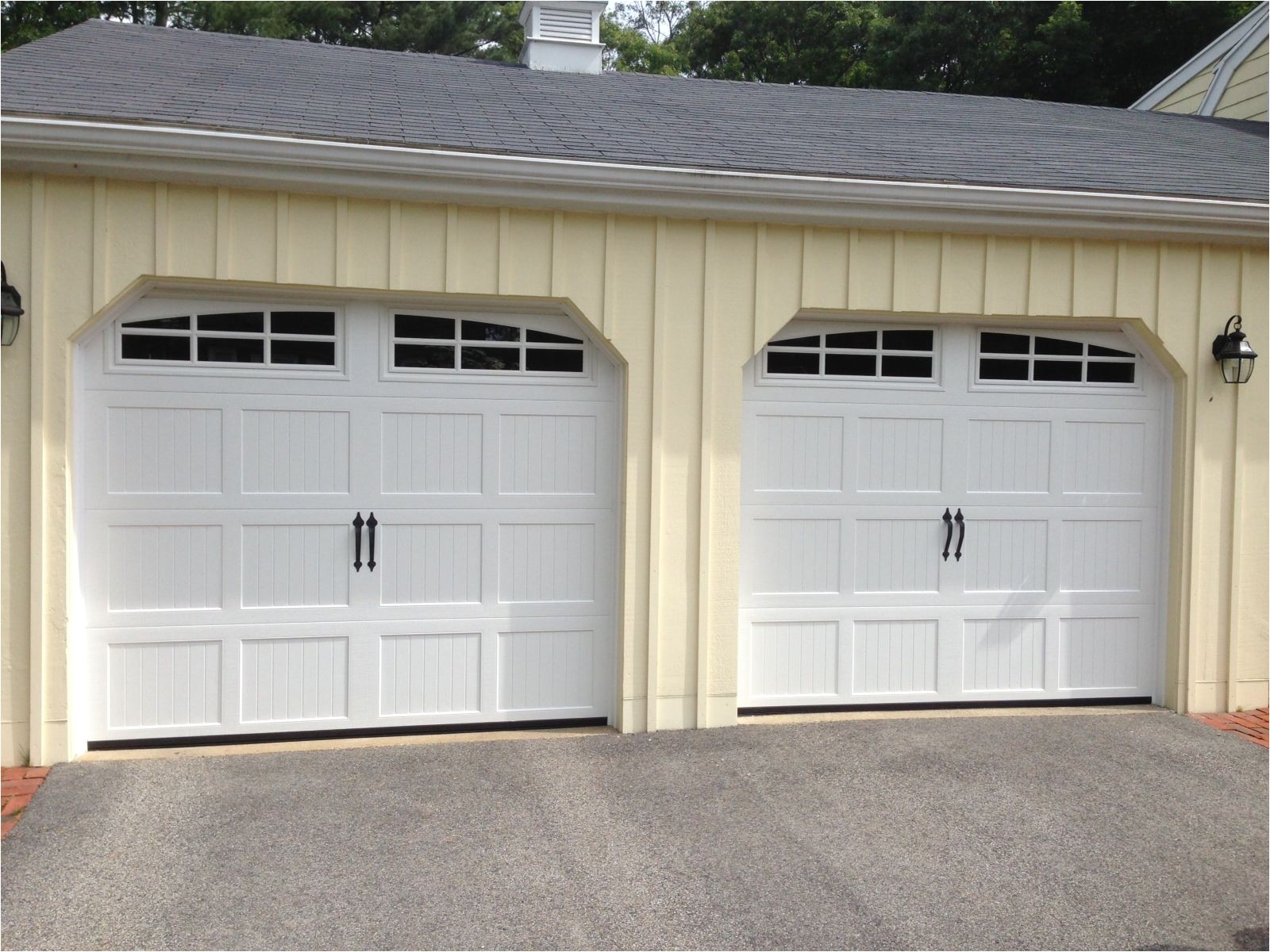 haas model 660 steel carriage house style garage doors in white with arch 6 pane glass flat black spade handles installed by mortland overhead door