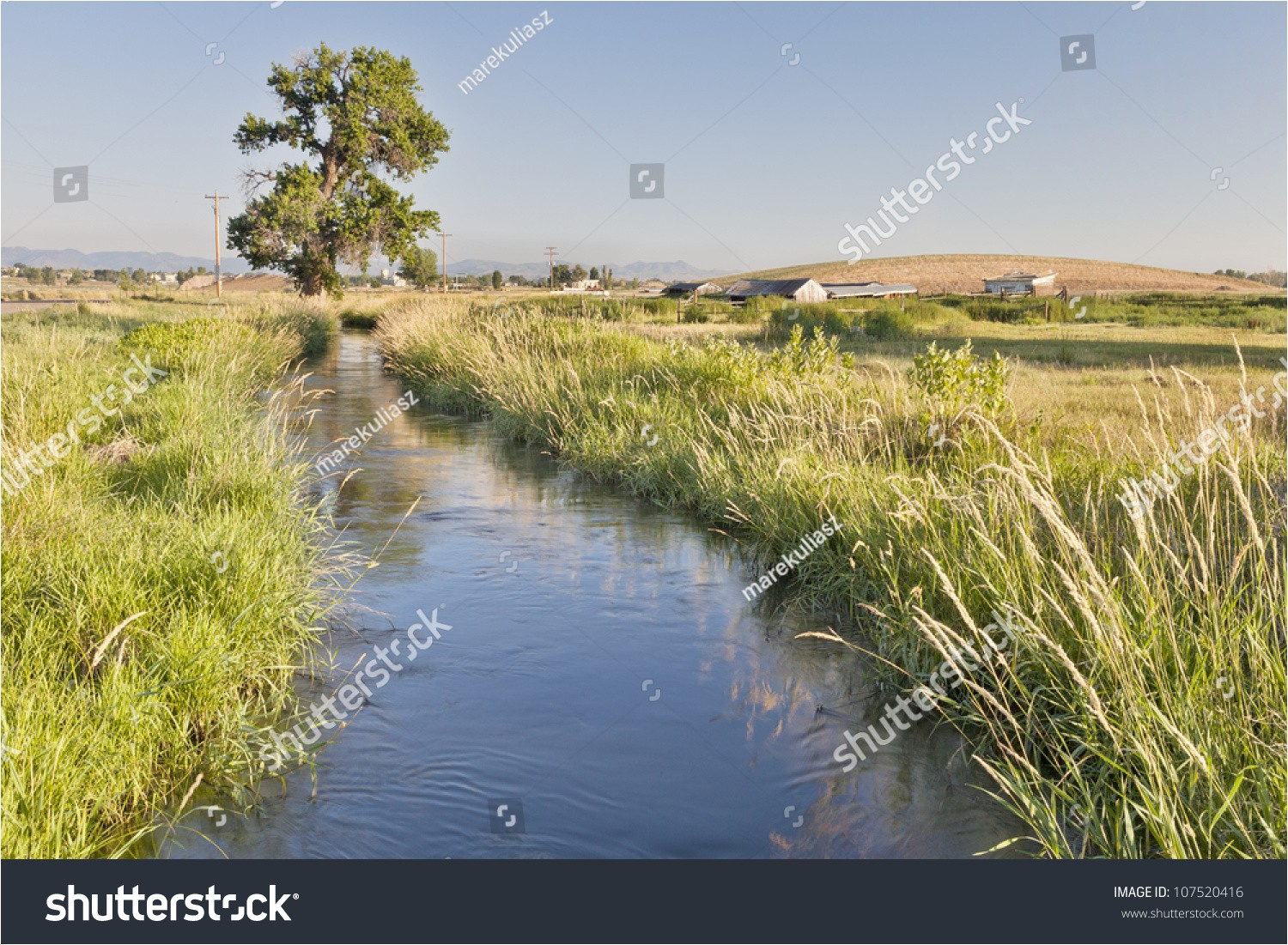 irrigation ditch in colorado farmland near fort collins with rocky mountains at a horizon summer