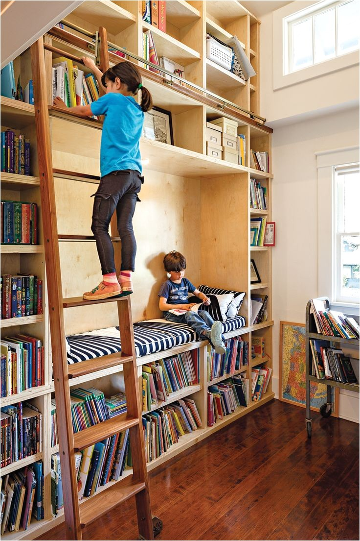 a former closet was transformed into a double height library complete with a reading nook and a rolling ladder perfect for children who love to read