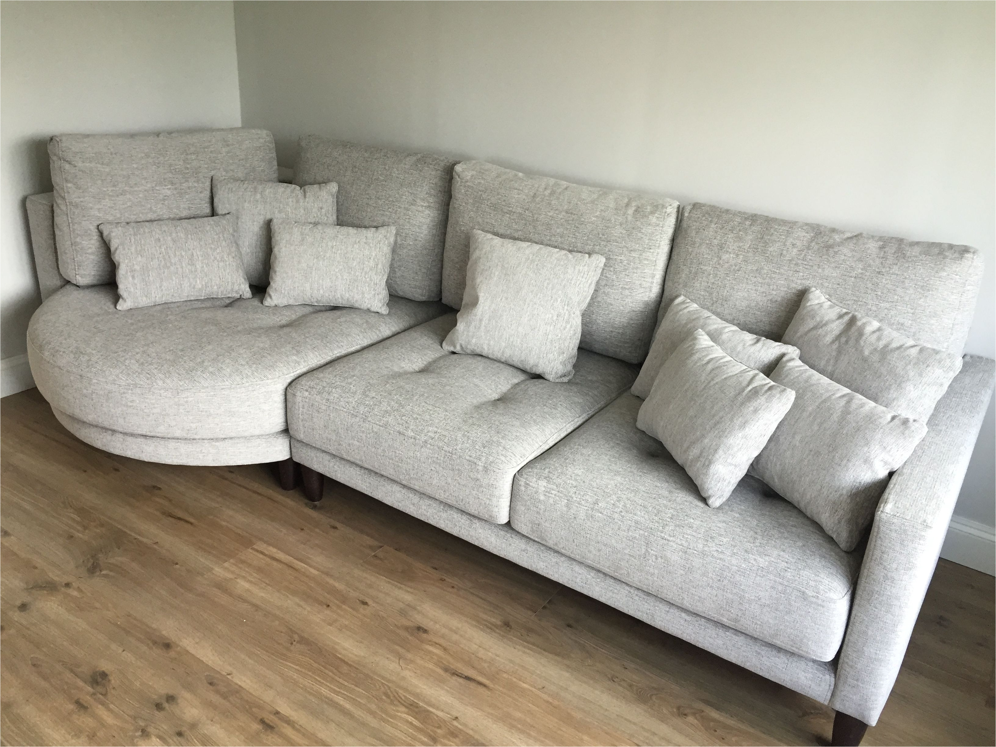 left hand facing rounded chaise with sofa section in light grey fabric and dark wood legs