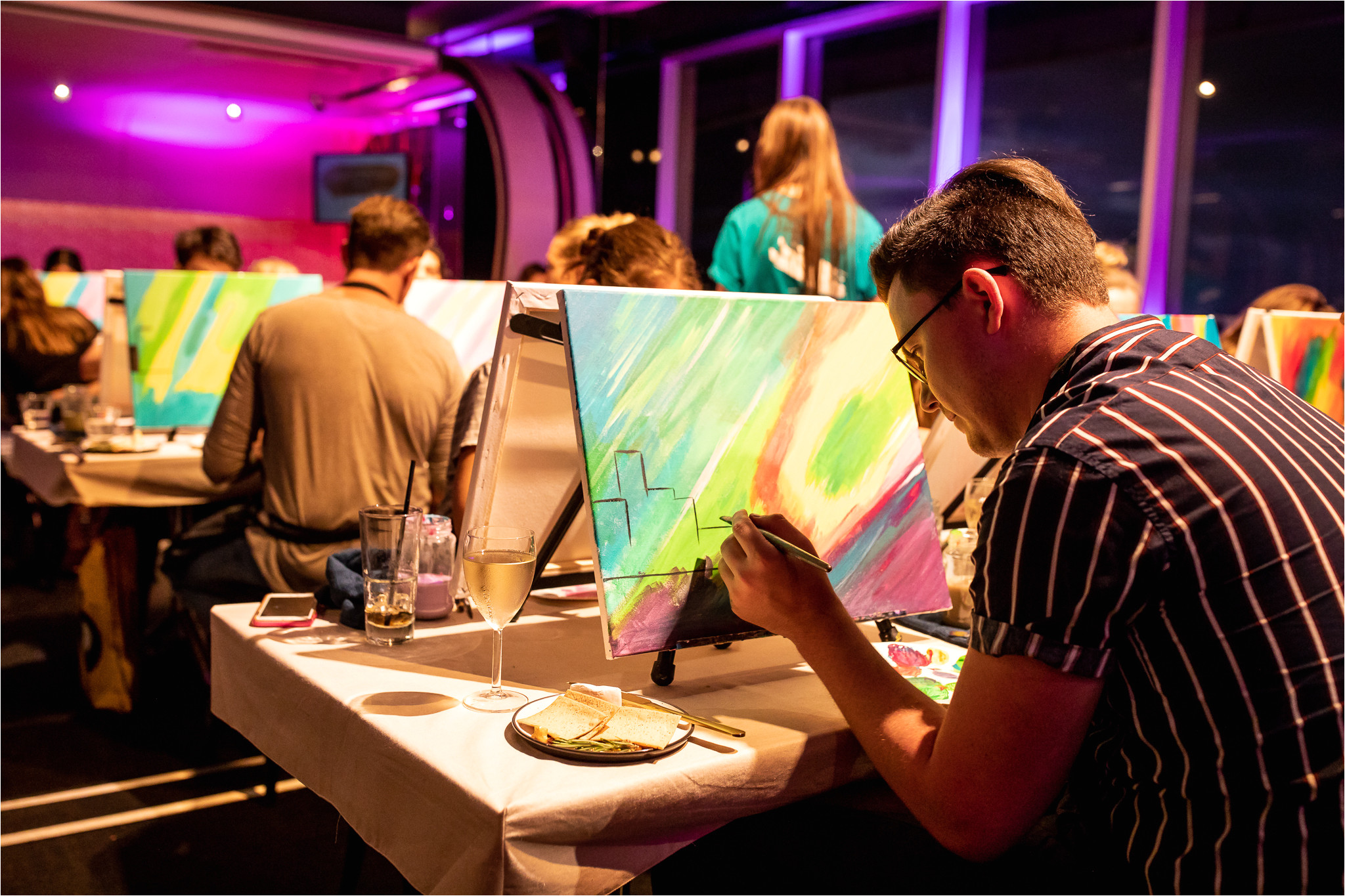 people painting on canvas and drinking wine