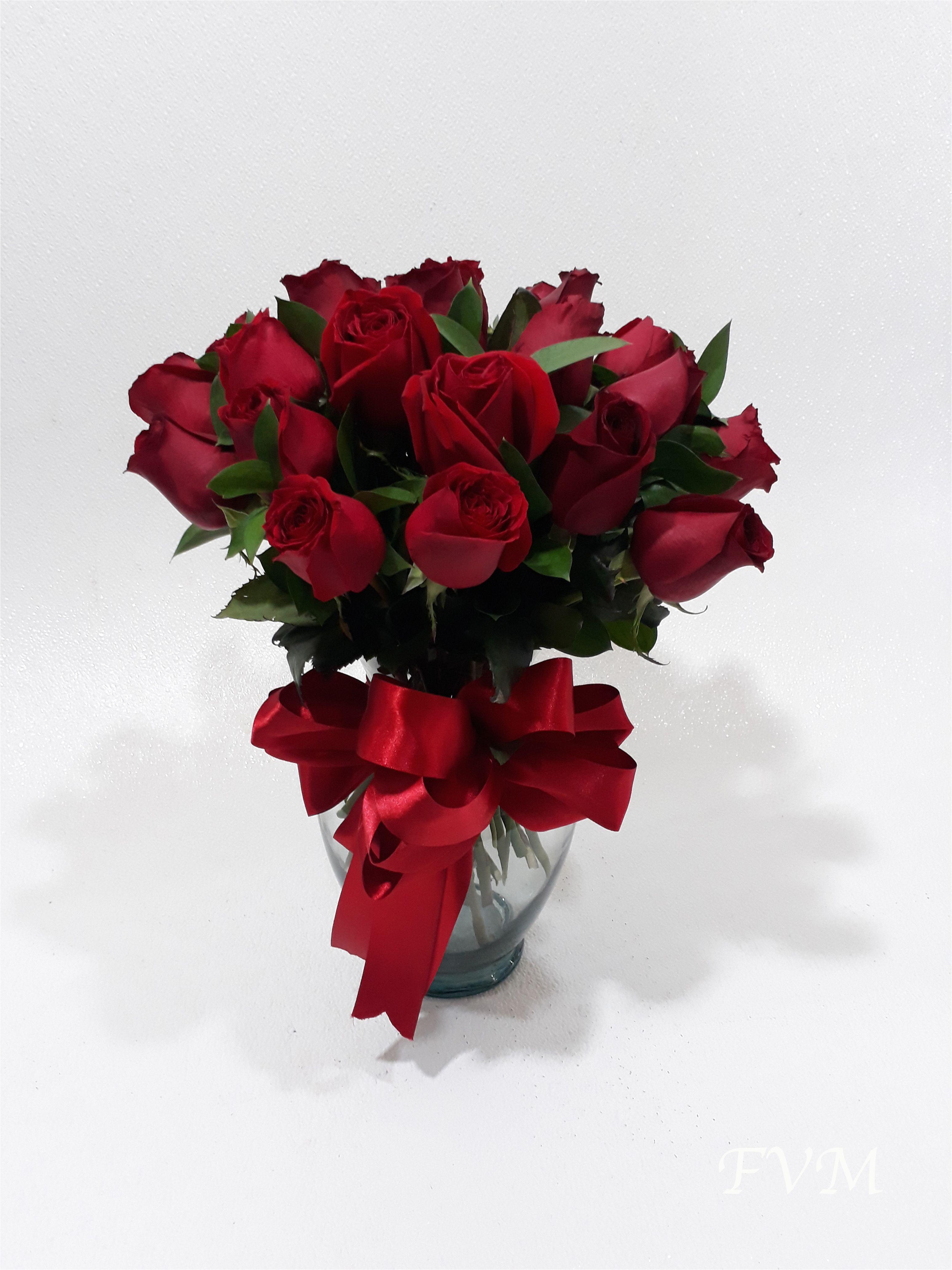 arreglo con 18 rosas rojas en base de cristal con follaje y
