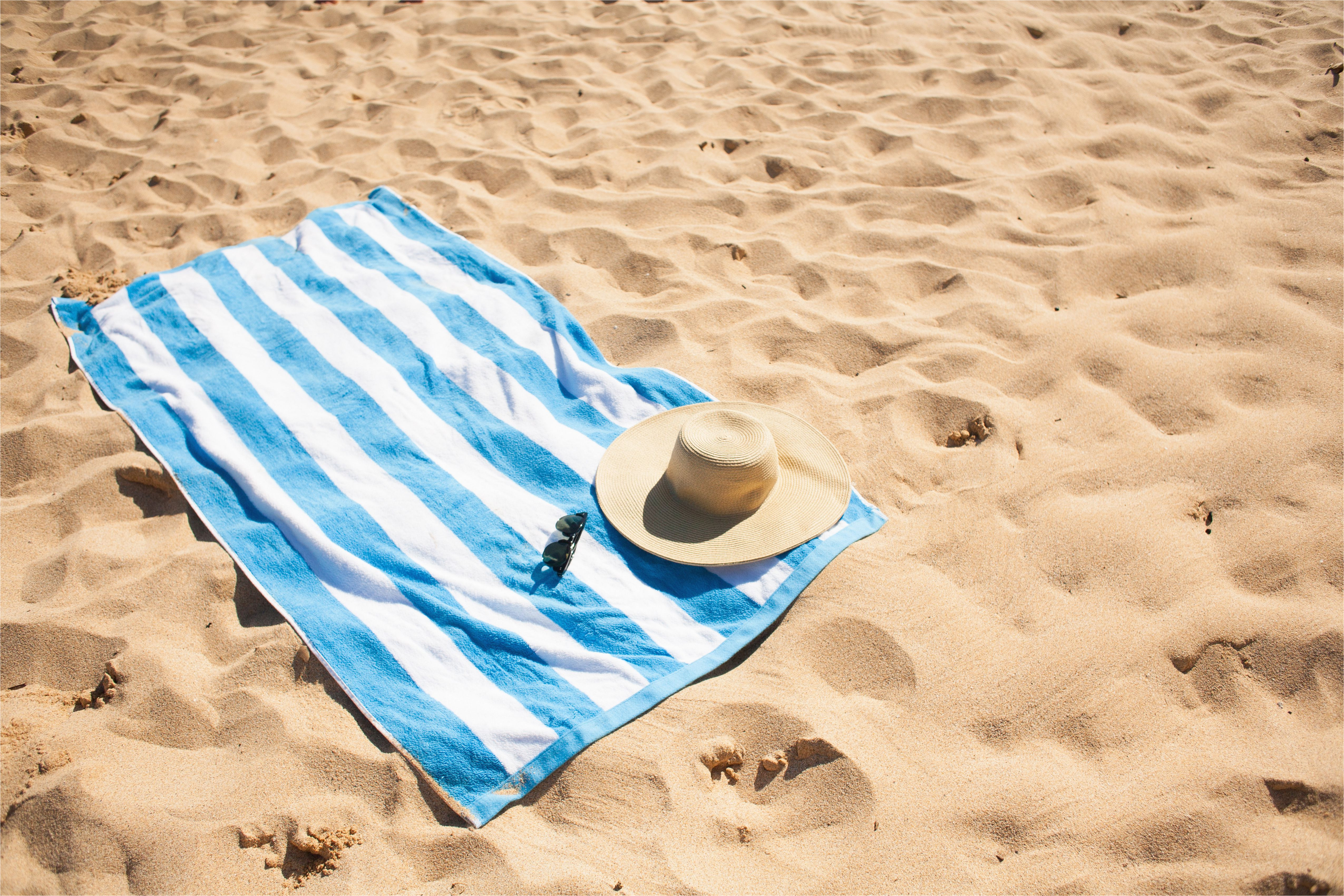 striped beach towel on sand with hat and glasses 463236755 5a1f20d5b39d030039f78644 jpg