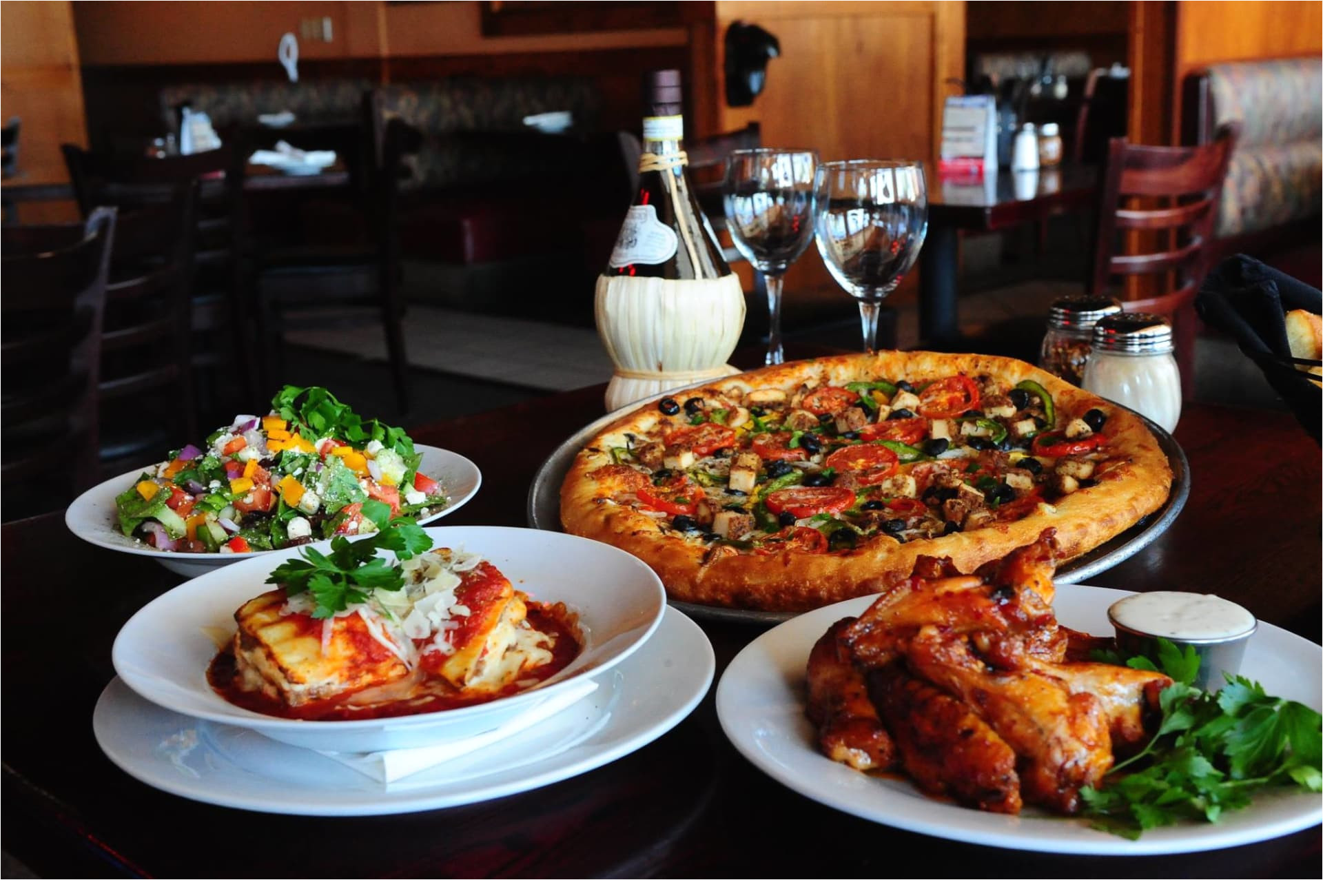 table with pizza lasagna salad and wings