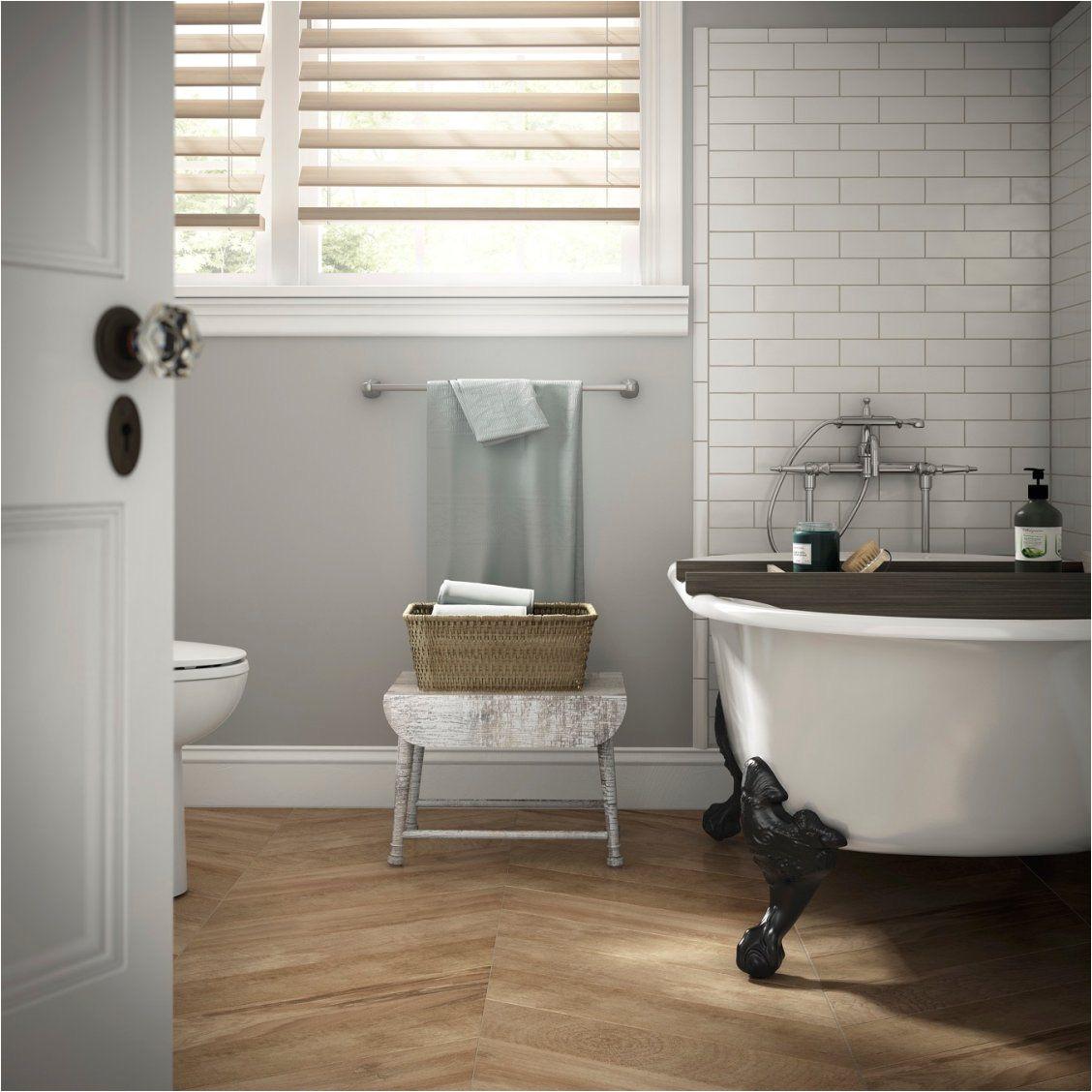 create a spa like bathroom with soft gray walls a clawfoot tub striking herringbone floors and classic white subway tiles around the tub
