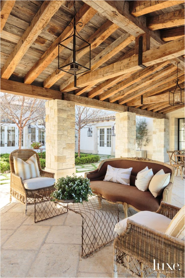 a cozy seating arrangement overlooks the courtyard with pavers from orange county stone lining its perimeter rattan chairs and an unusual wire grid coffee