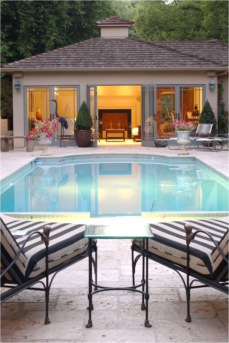 view of a lighted pool house next to an inground swimming pool with two loungers in the foreground