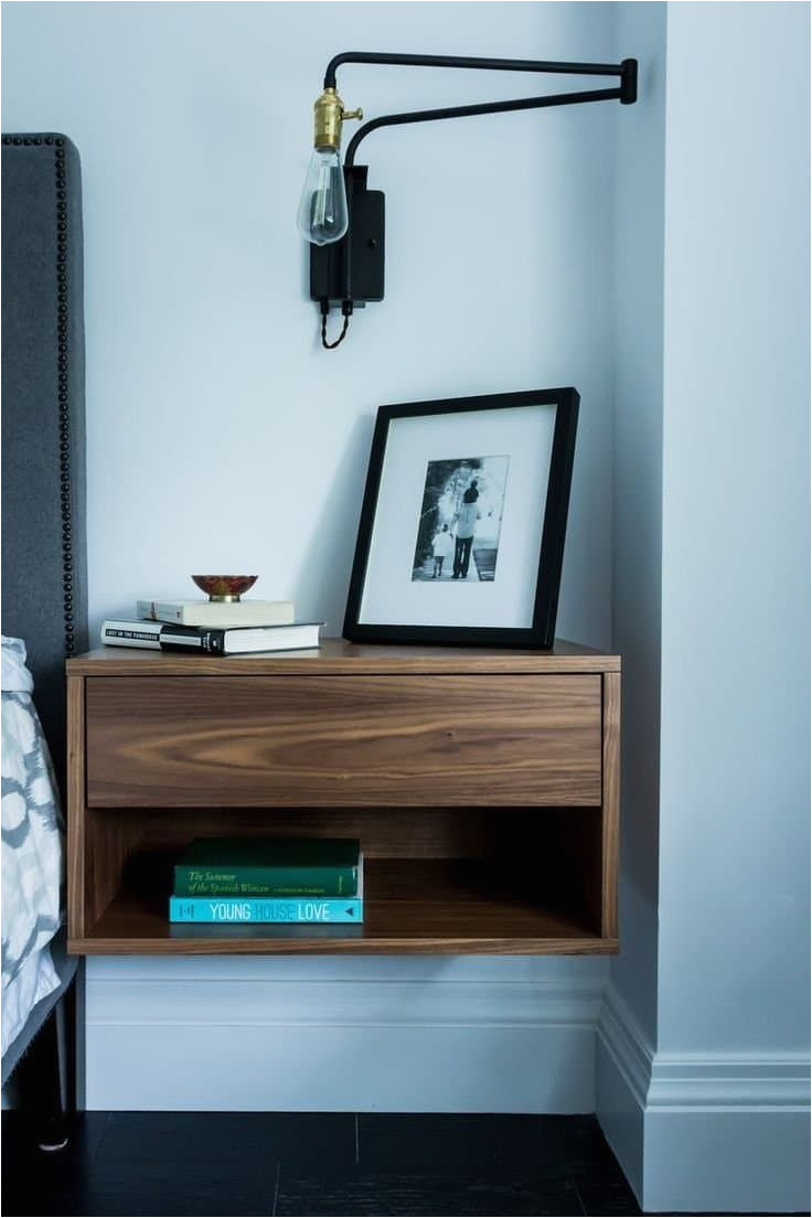 floating modern wood nightstand with swing arm sconce and photo frame