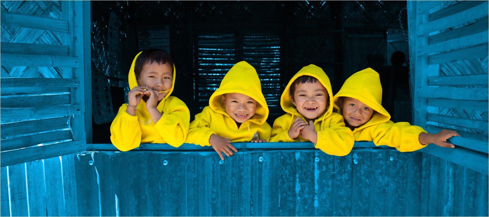 four children look out an open window bangladesh