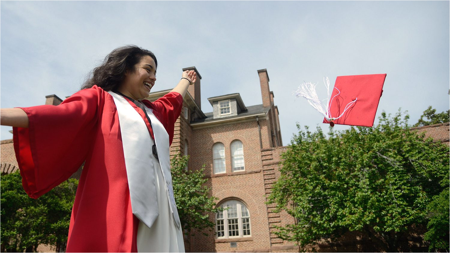 an nc state graduate throws her cap in front of holladay hall