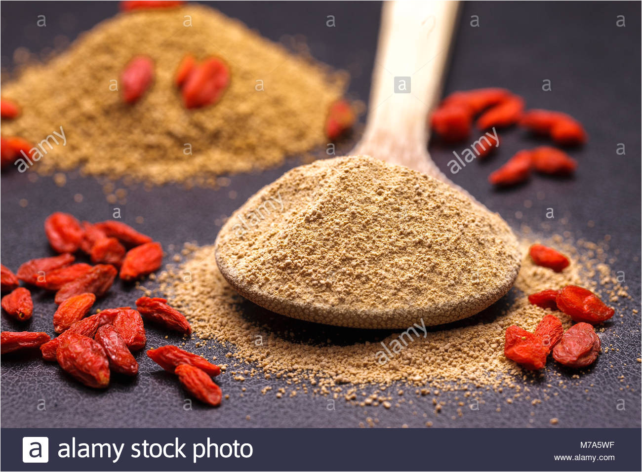 ground up pure cane sugar on a wooden spoon and red goji berries stock