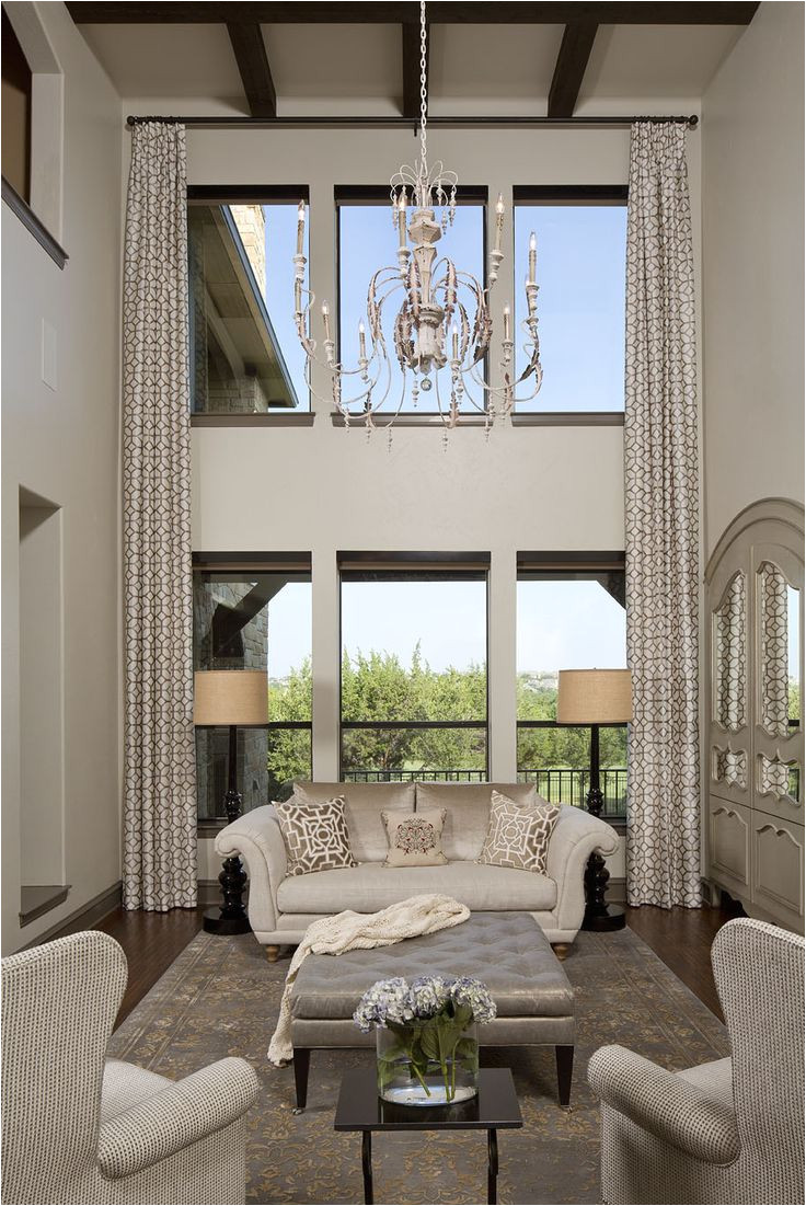 custom two story geometric embroidered draperies frame the living room windows the room is