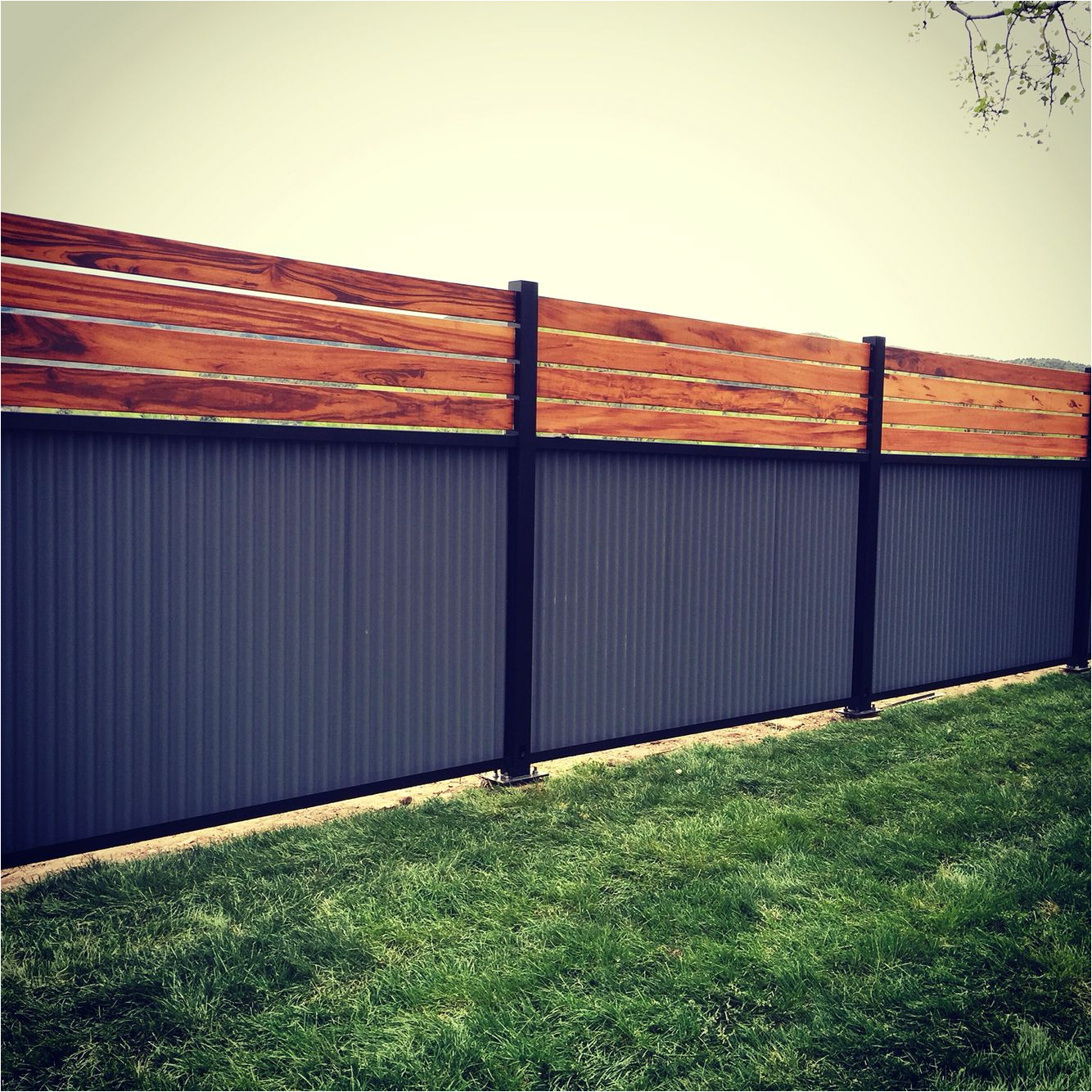 custom privacy fence built out of metal post tiger wood and corrugated metal