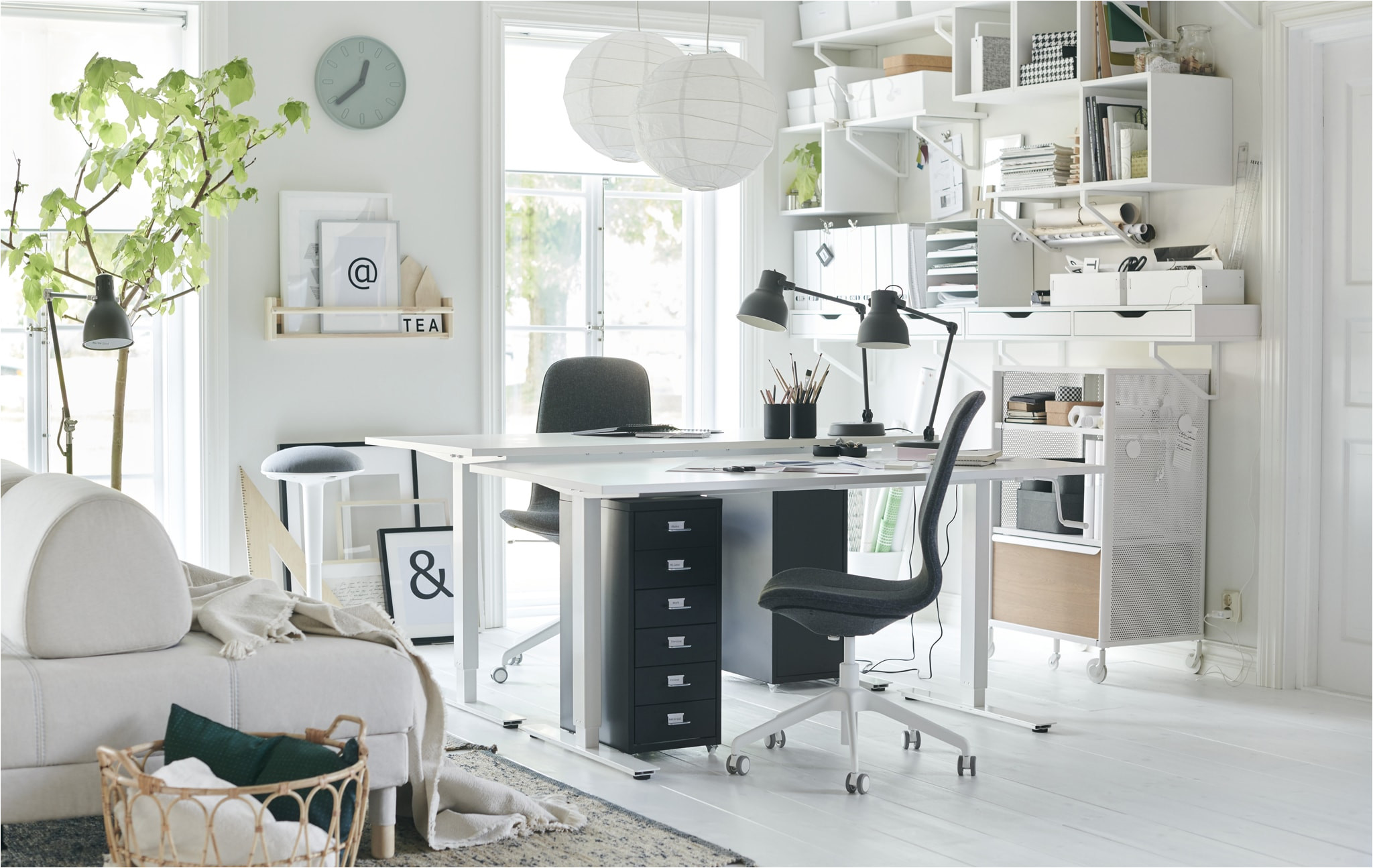 two desks and desk chairs in the corner of a white living room with wall storage