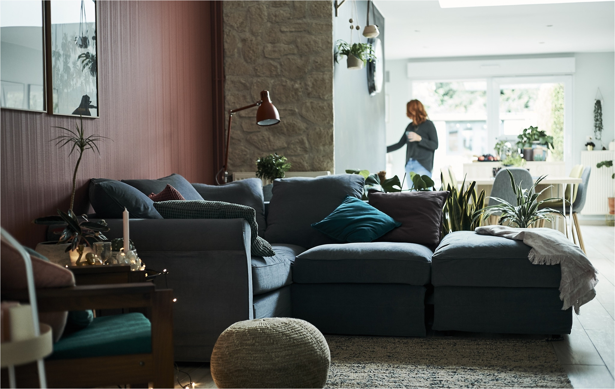 a living room with l shaped grey sofa and red wall with a dining