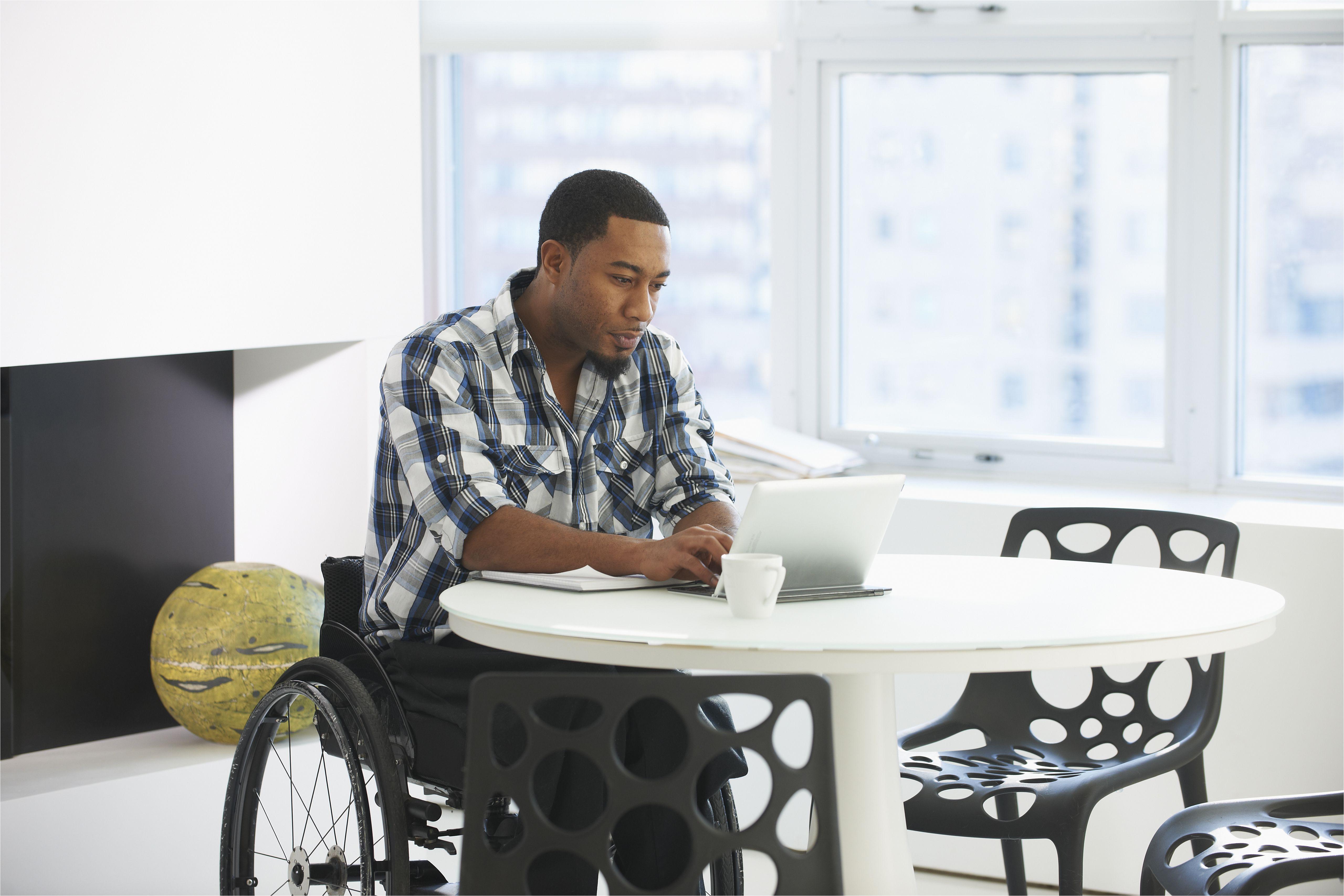 black businessman in wheelchair using laptop at table 672161631 5a6b3a3a43a1030037040e7e jpg
