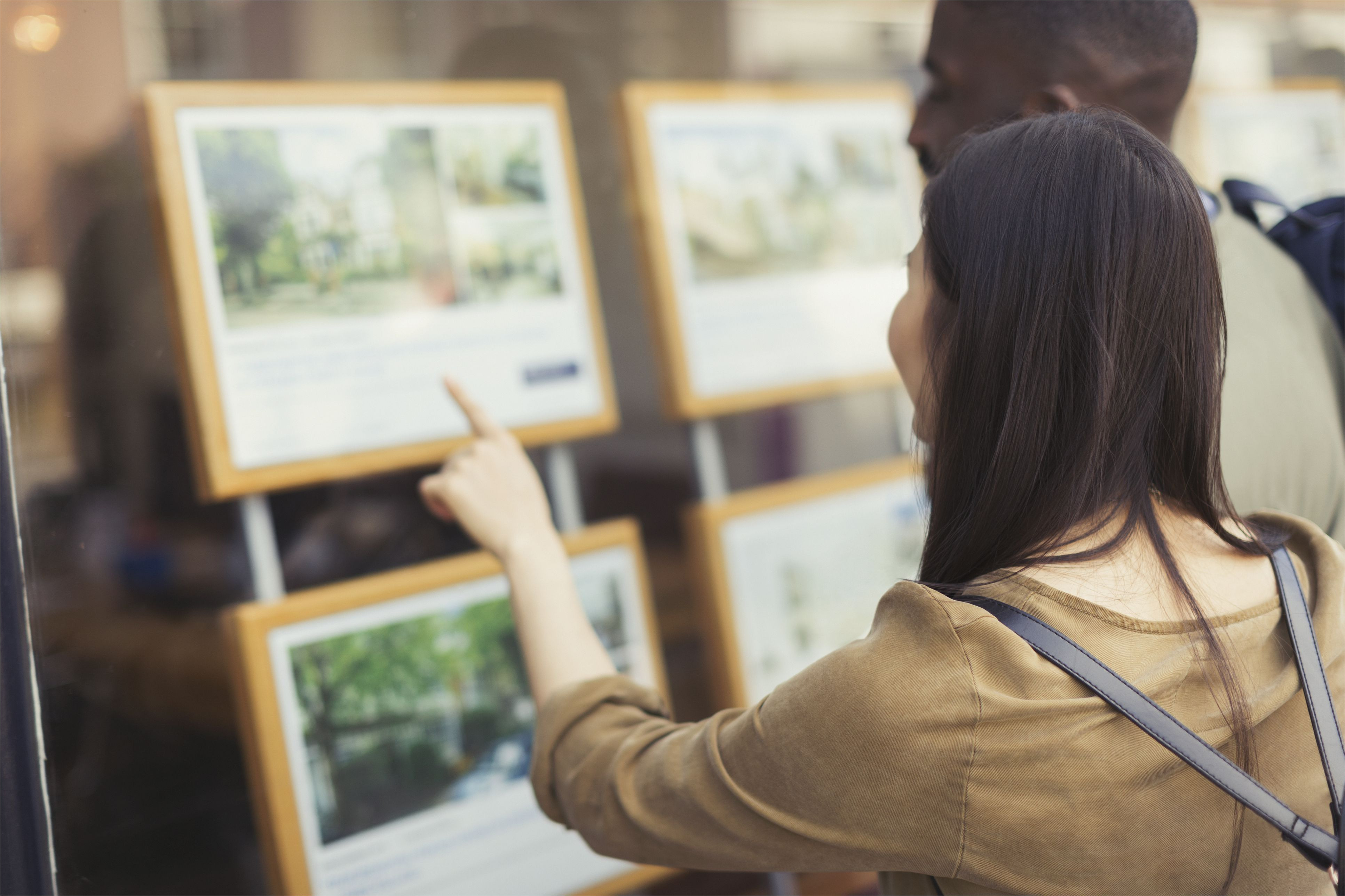 young couple browsing real estate listings at storefront 906503752 5a9e16593de423003731405a jpg