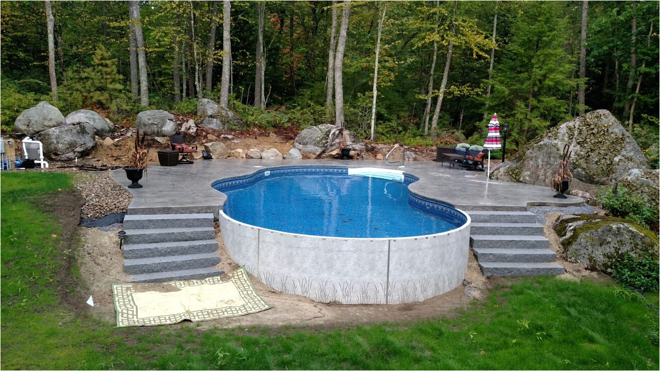 radiant 18x32 freeform built into a hill with stamped concrete deck and walk in steps