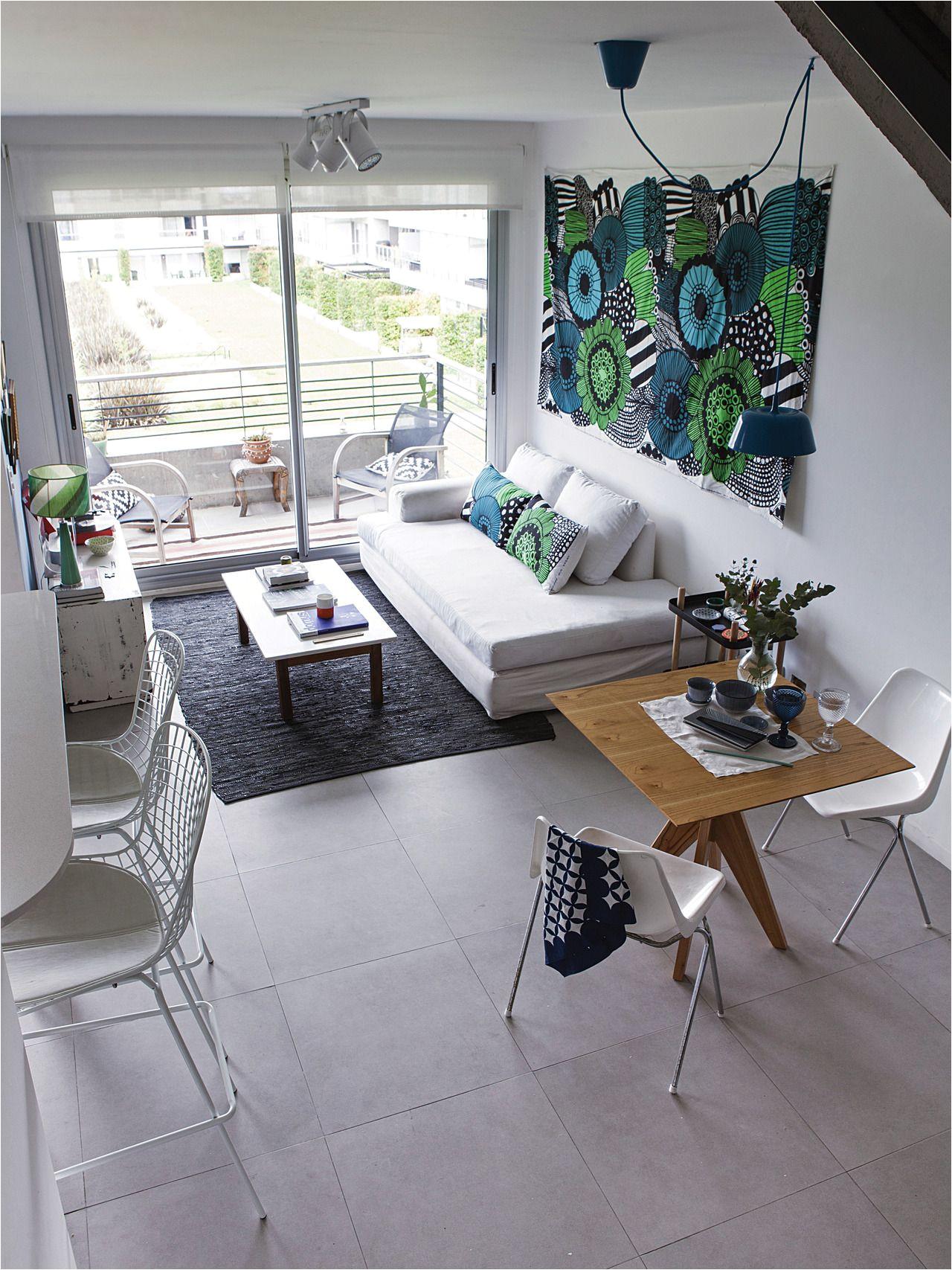 living comedor y cocina integrados en la planta baja de un duplex con gran genero de marimekko como mural en la pared