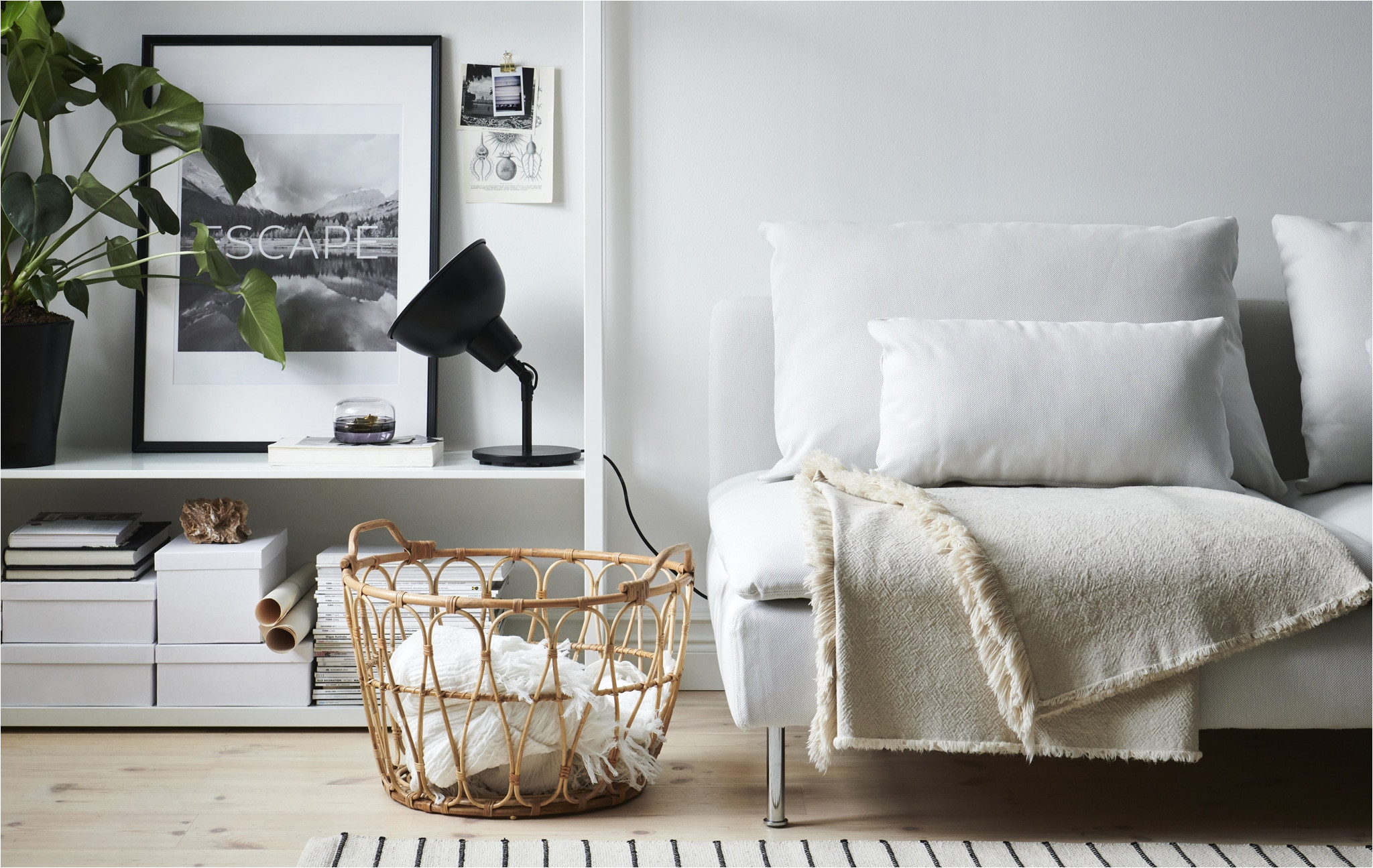a living room with white sofa black lamp open storage unit and wicker basket