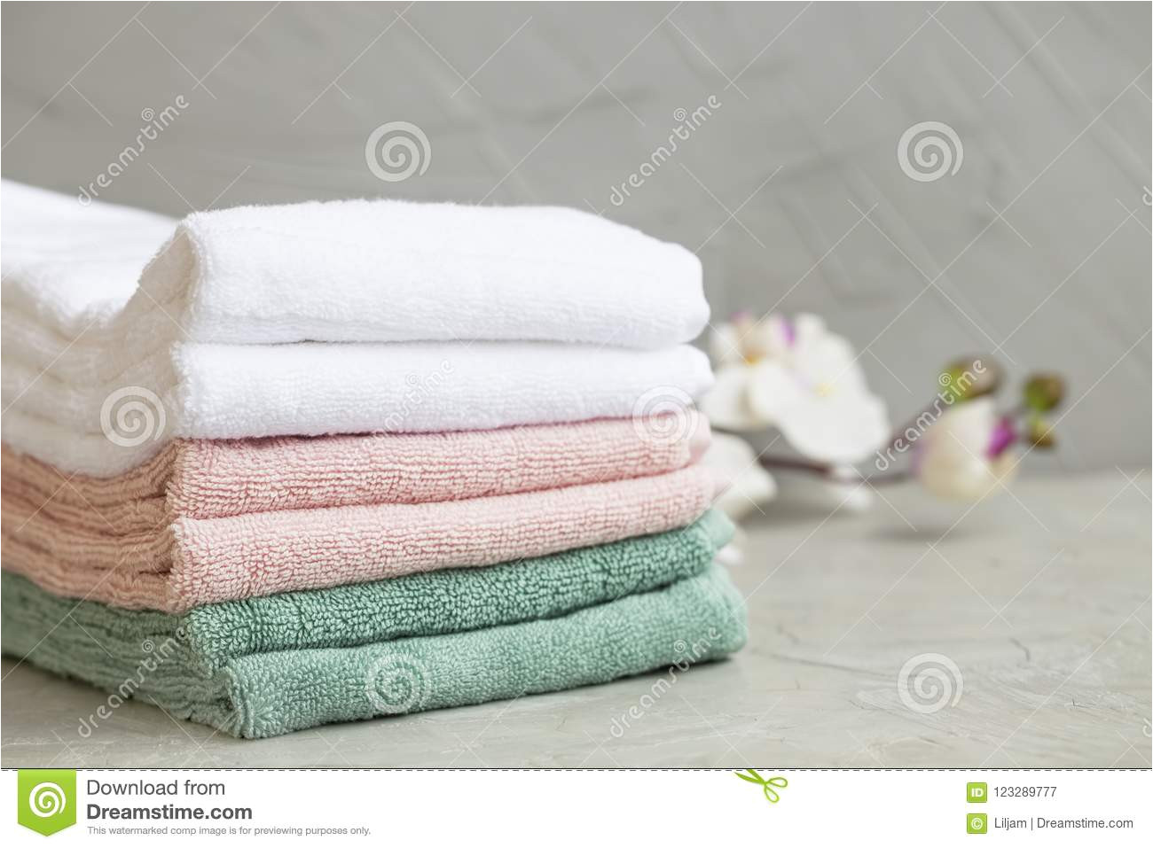 pile of clean cotton bath towels on concrete background laundry or bathroom concept