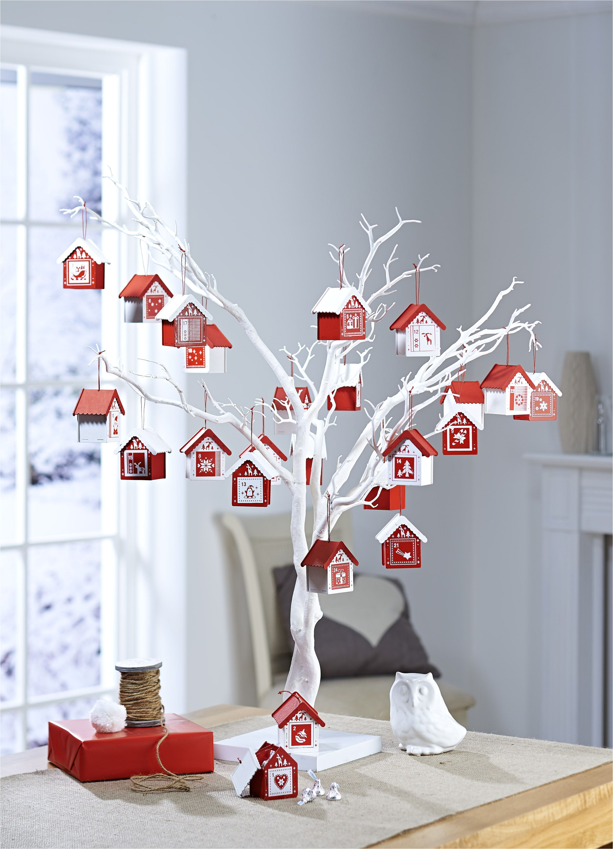 bored of the usual cardboard advent calendars with chocolate button inserts well how about this idea for a change advent houses on a white twig tree from