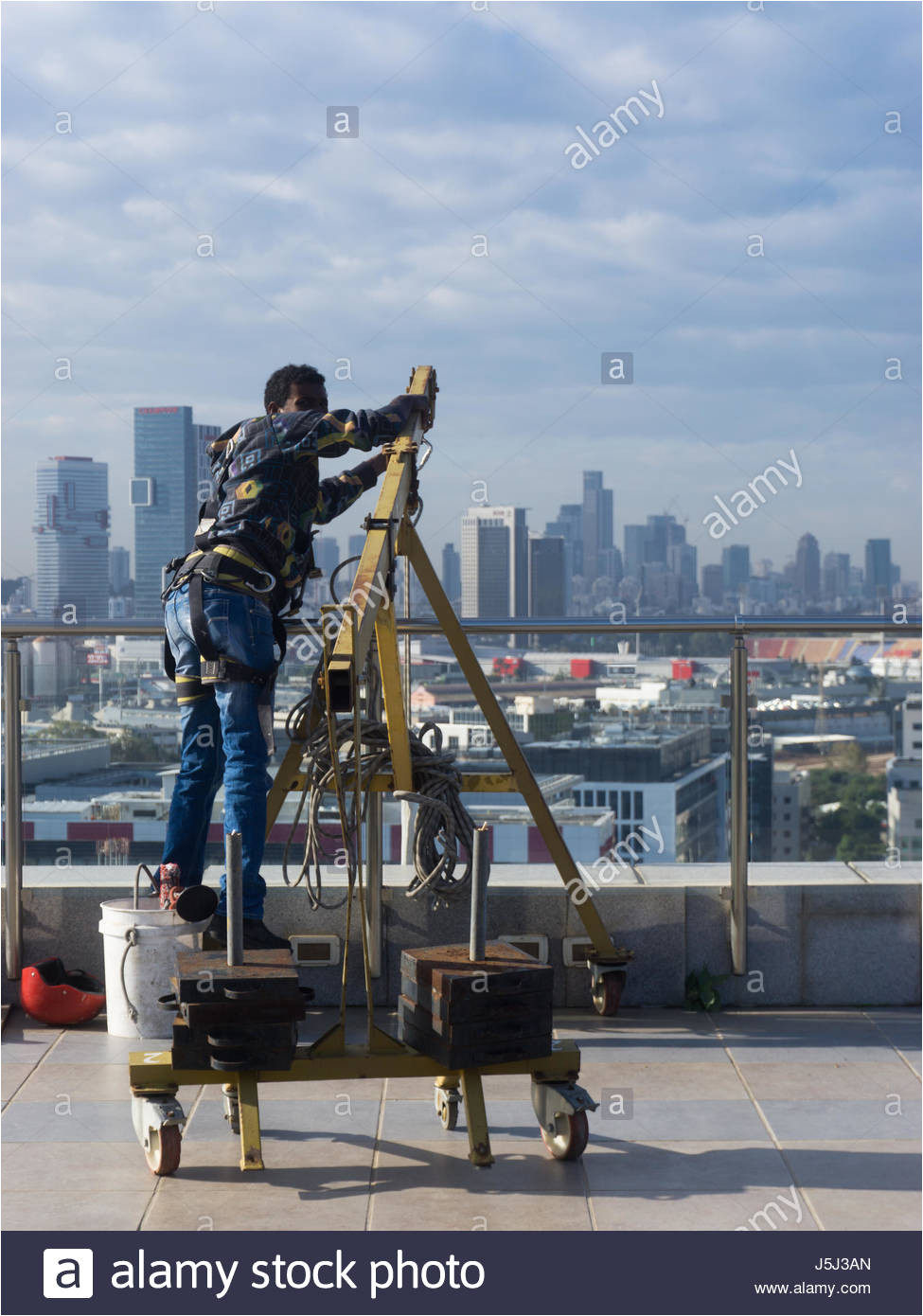 window cleaning employee with work tools and city background stock image