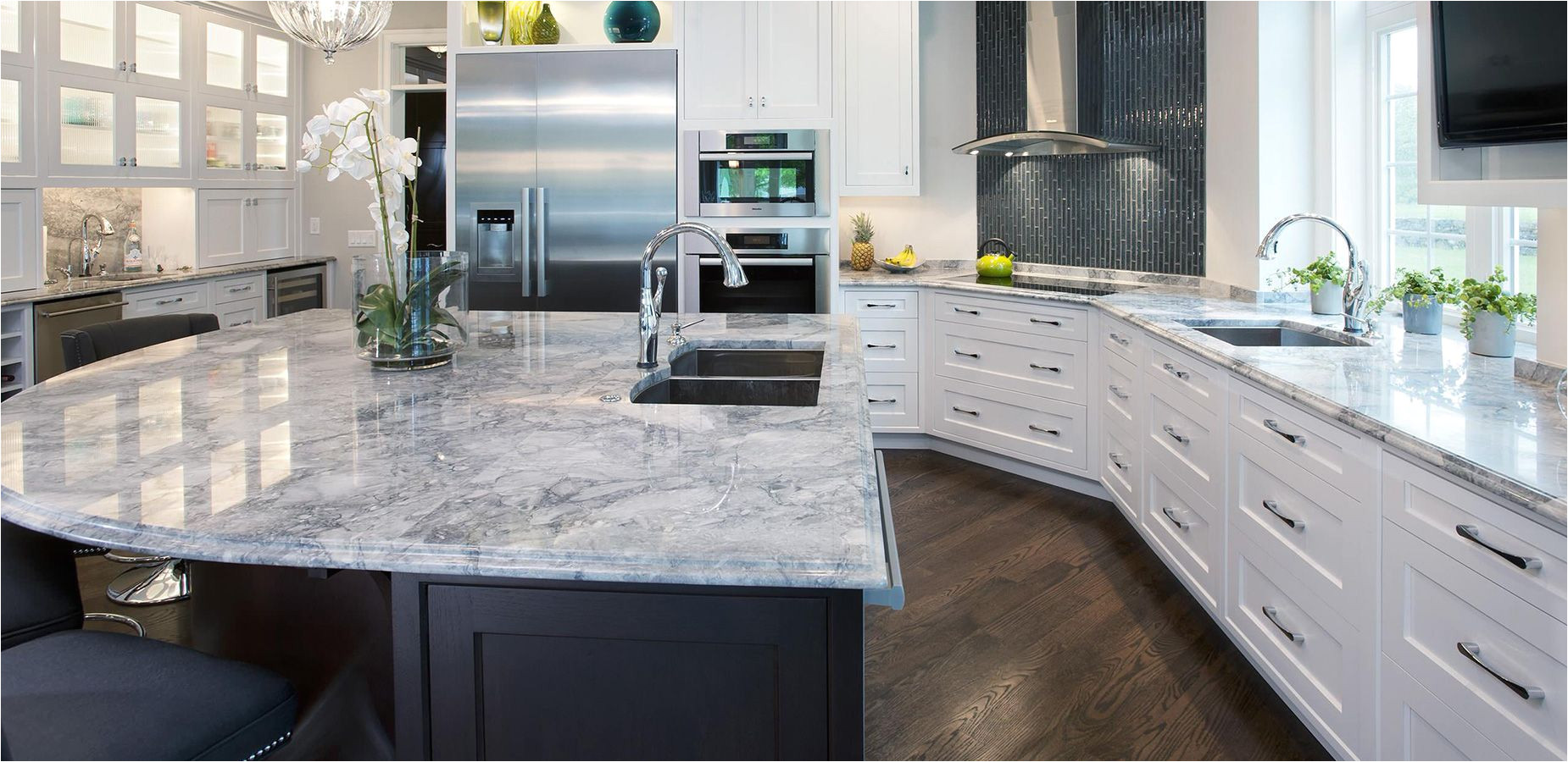white fantasy countertop with black island and white cabinets and black glass mosaic tile