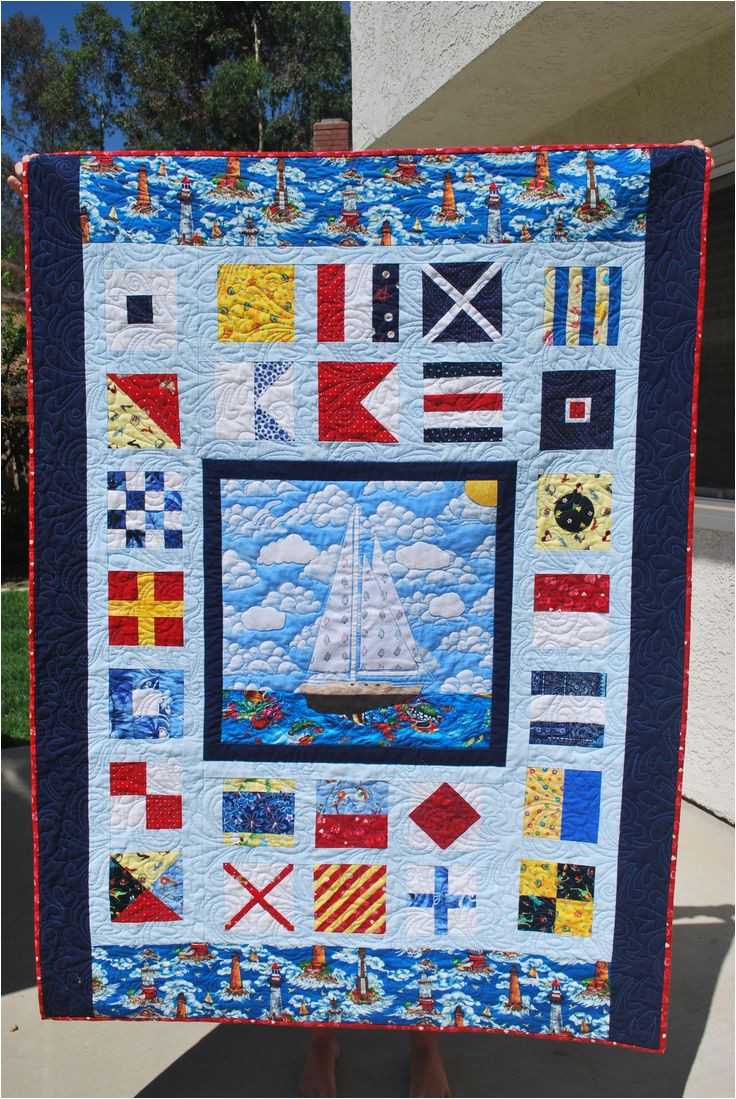 custom nautical quilt for my sister all a z nautical flags and her boat appliqued in the center made with scraps fabrics in the red blue yellow