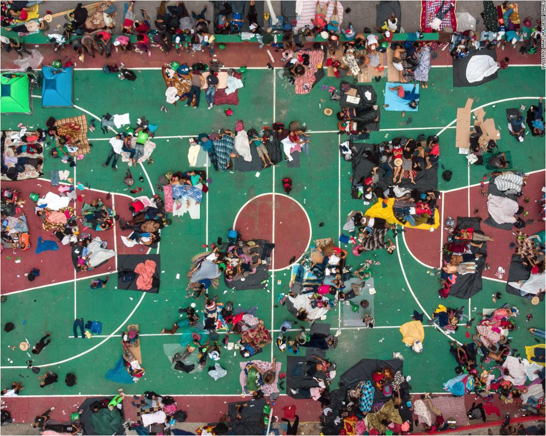 migrants heading in a caravan to the united states rest on a basketball court in san
