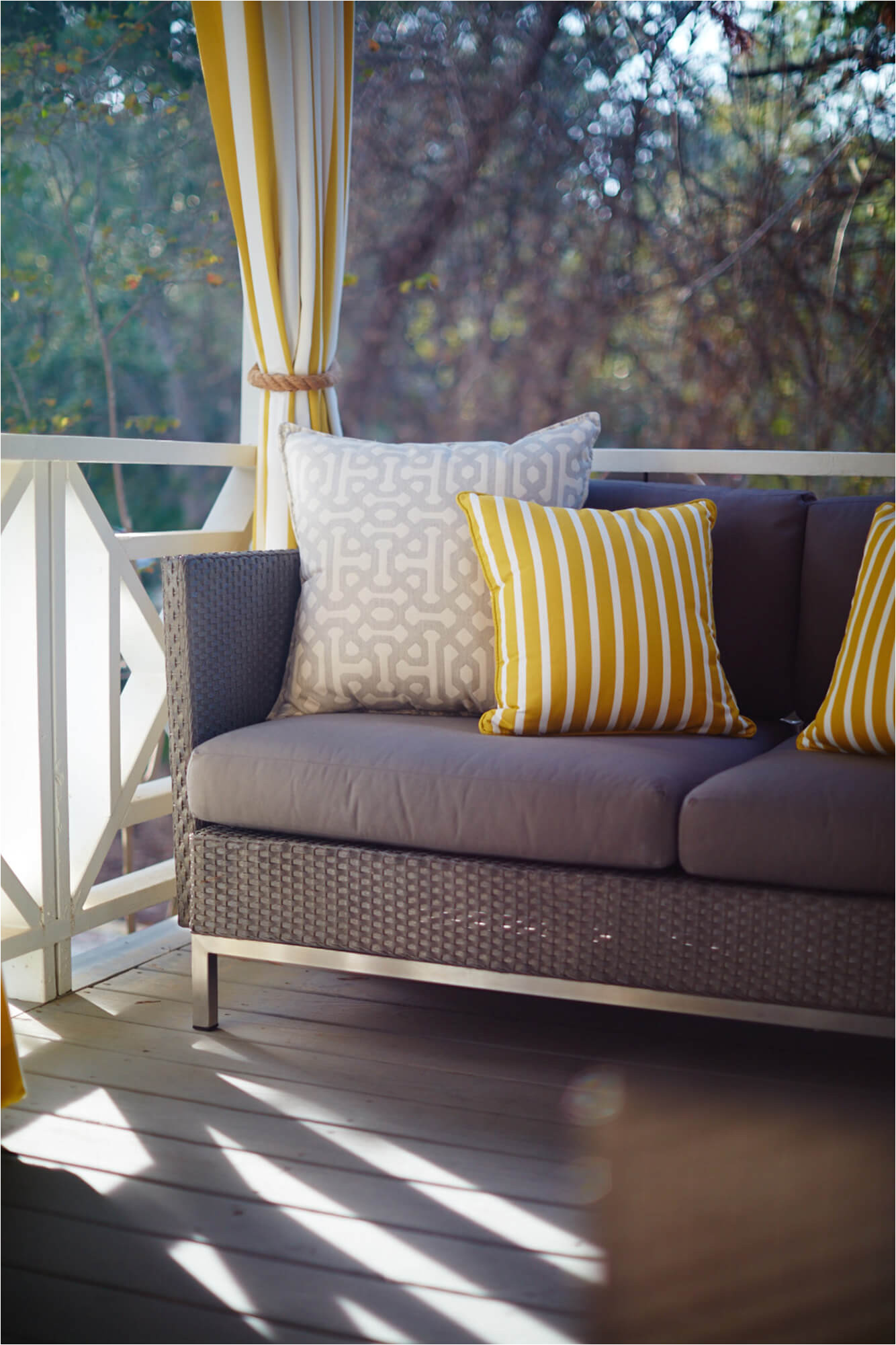 outdoor sofa with yellow and grey decorative throw pillows and yellow and white striped drapery outdoor drapery in