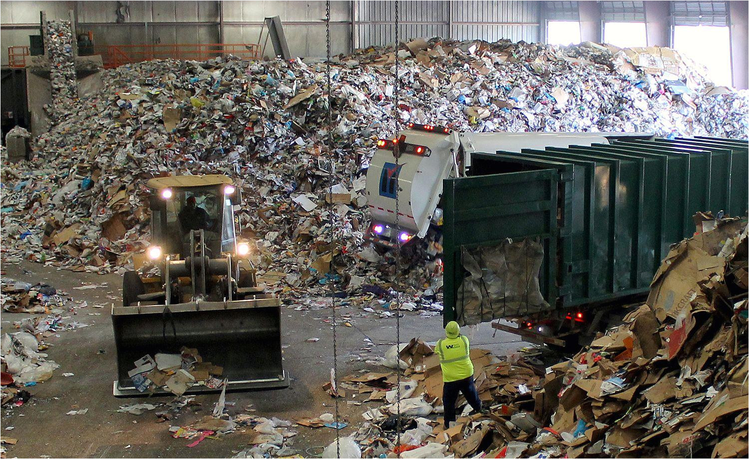 trucks dump their loads of single stream recycling on the tip floor at resource management s materials recovery facility mrf in earth city mo