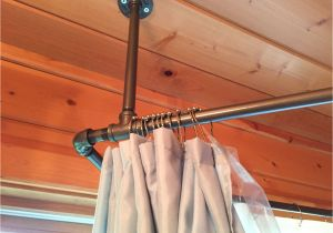 Sloped Ceiling Closet Rod Support Used Black Iron Piping to Create A Shower Curtain Rod that Surrounds